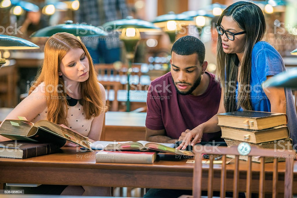 Three students in a public library stock photo