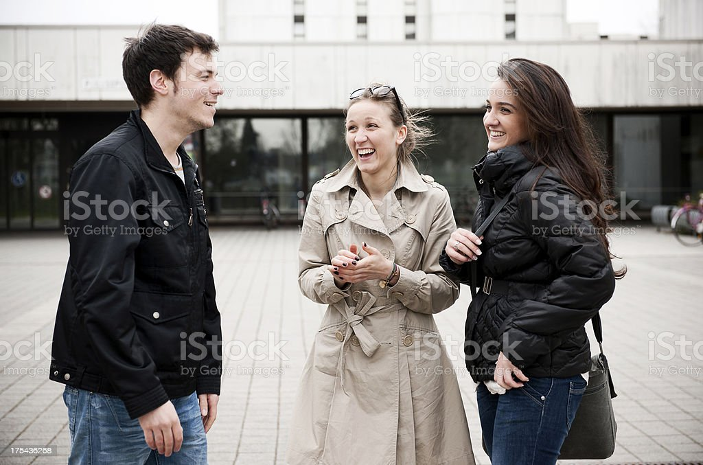 Three students standing on campus stock photo