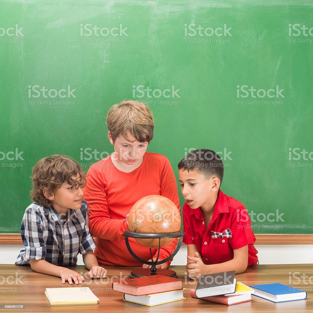 Three Students Working On Navigation Map Globe stock photo