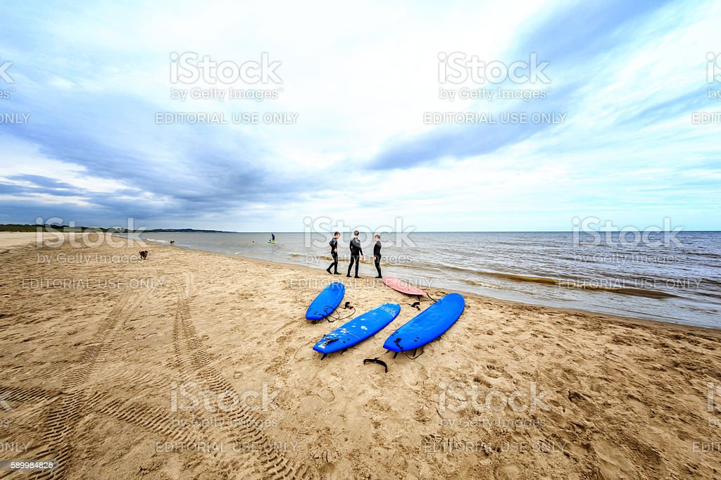 Three surfers on the seashore with blue surfboards stock photo