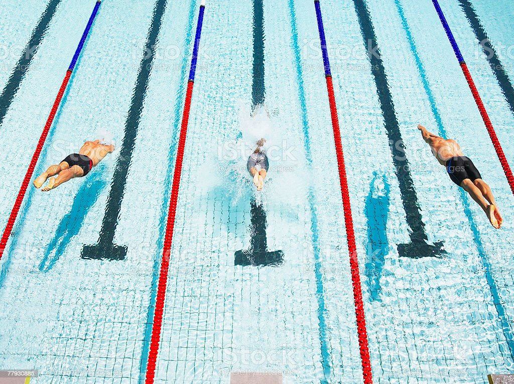 Three swimmers diving in pool royalty-free stock photo