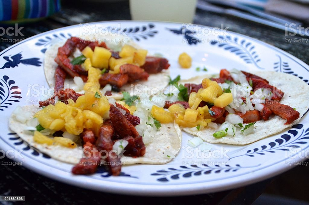 Three tacos al pastor on corn tortillas stock photo