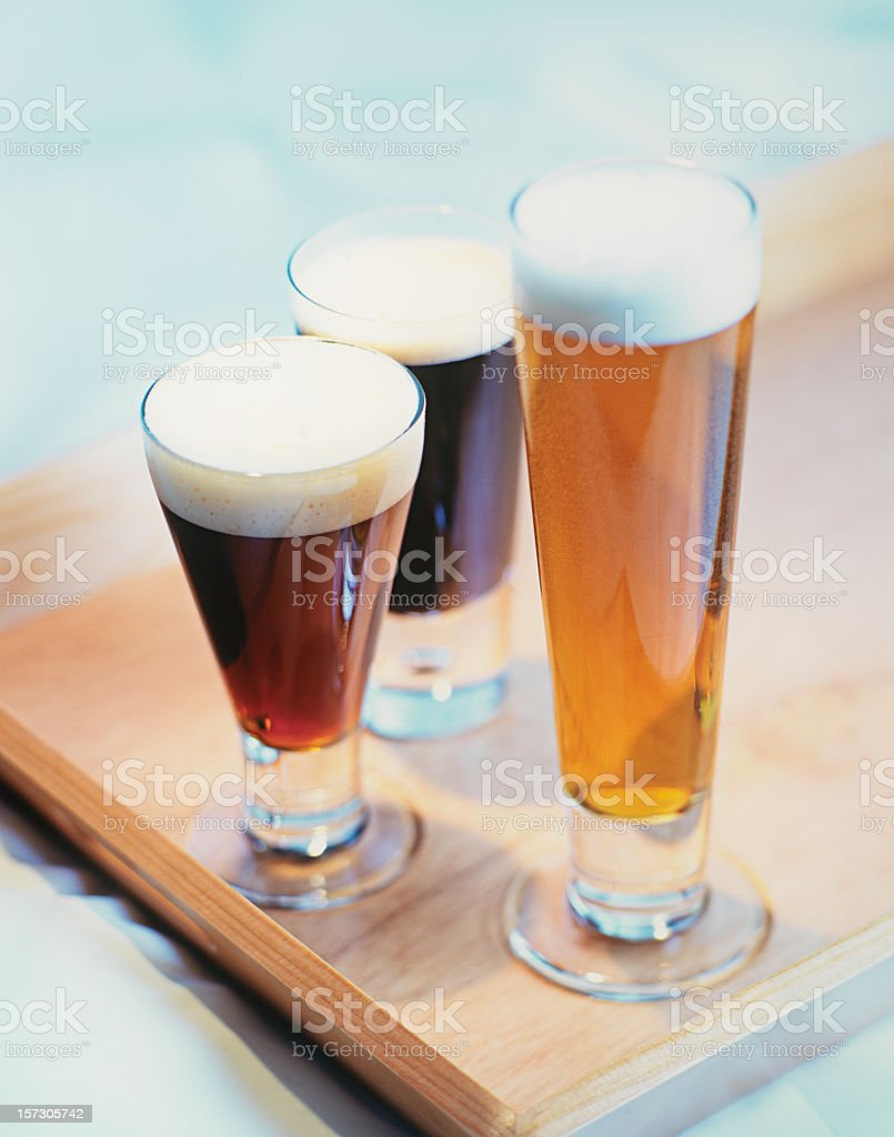 Three tall glasses of craft beers in wooden board royalty-free stock photo