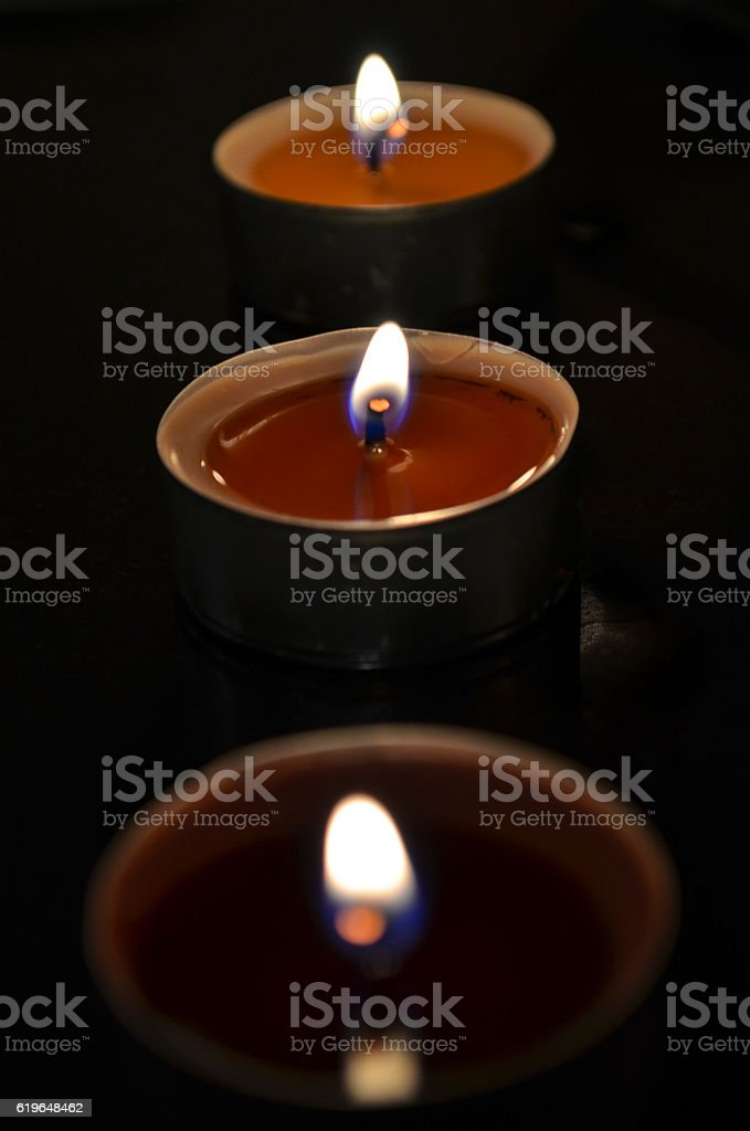 Three tea lights glowing in the dark with red wax stock photo