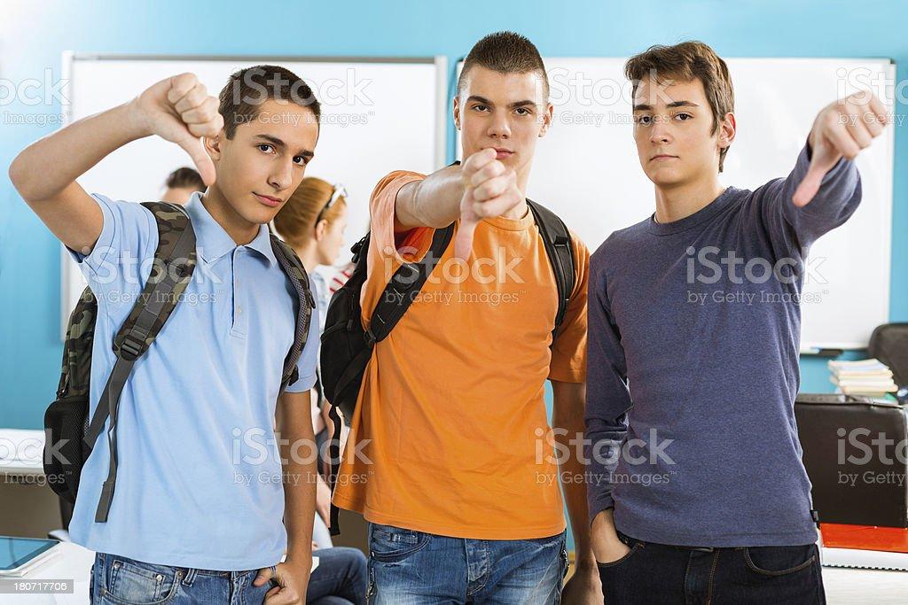 Three teenage boys showing thumbs down royalty-free stock photo