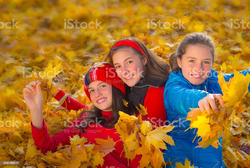 Three teenage girls among yellow leaves. Autumn royalty-free stock photo