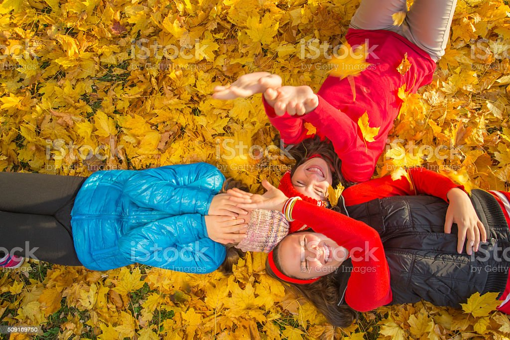 Three teenage girls among yellow leaves. Autumn royalty-free stock photo