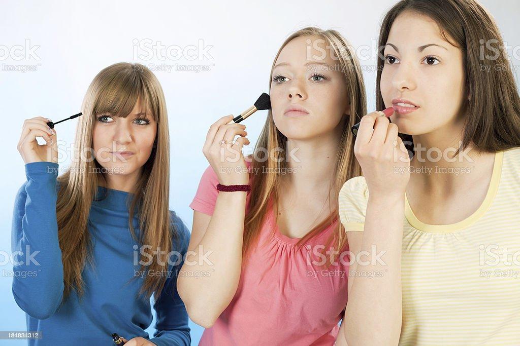 Three teenage girls applying a make-up royalty-free stock photo