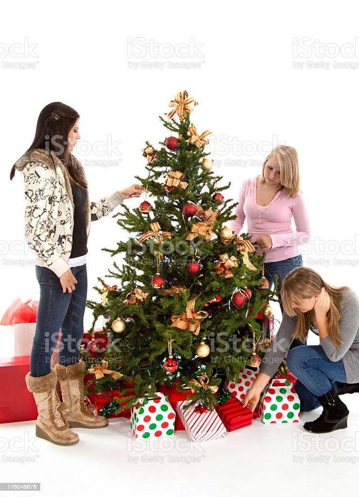 Three teenage girls around a Christmas tree with gifts. royalty-free stock photo
