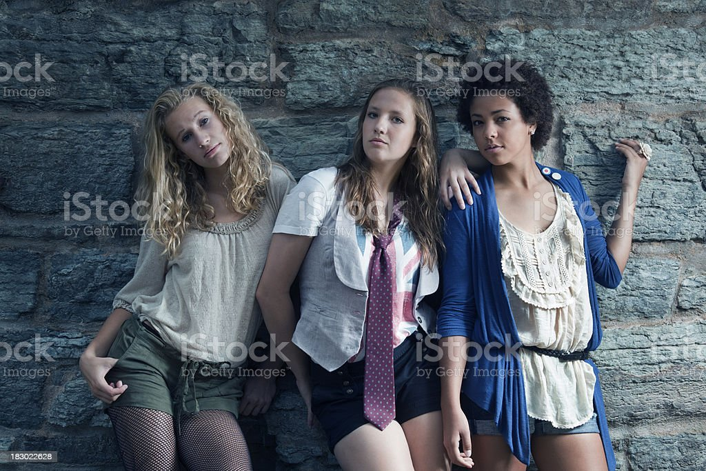 Three Teenage Girls, Young Women Looking Cool by Stone Wall royalty-free stock photo