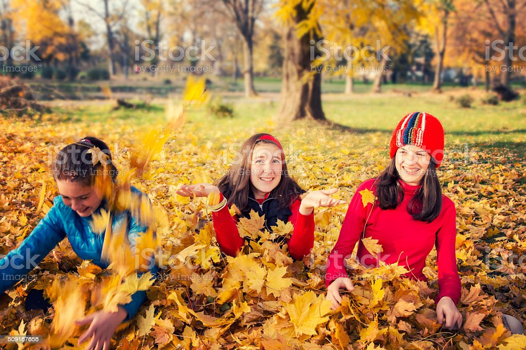 Three teenage playing with yellow leaves in autumn royalty-free stock photo