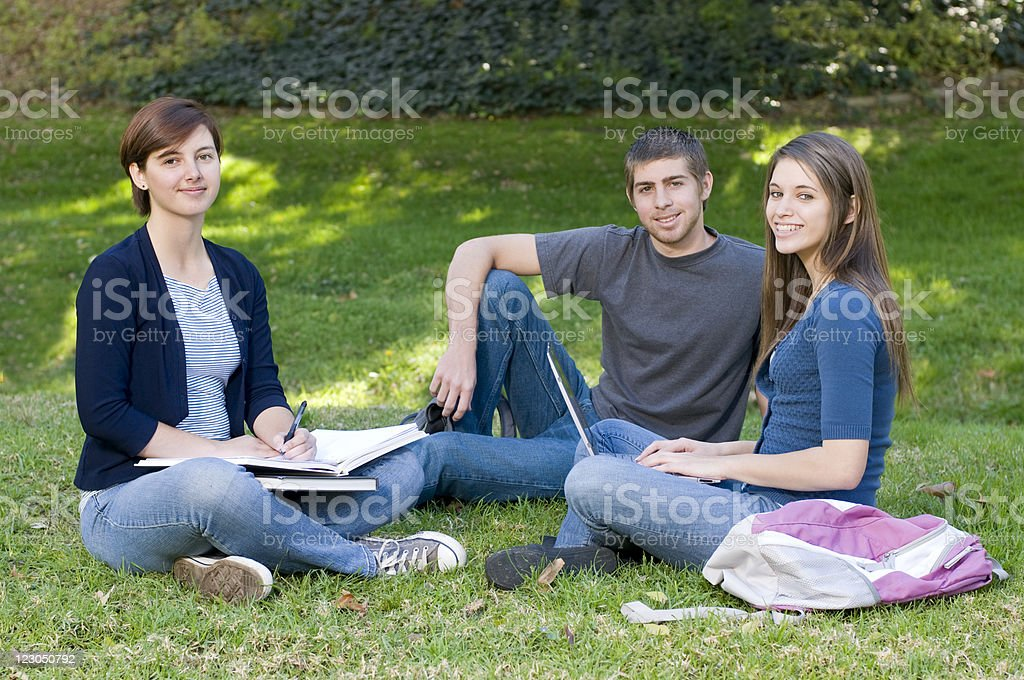 Three Teenage Students Sitting and Posing for the Camera royalty-free stock photo
