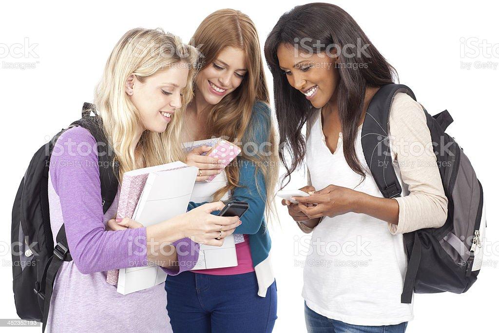 Three teenage students using mobile phones. royalty-free stock photo