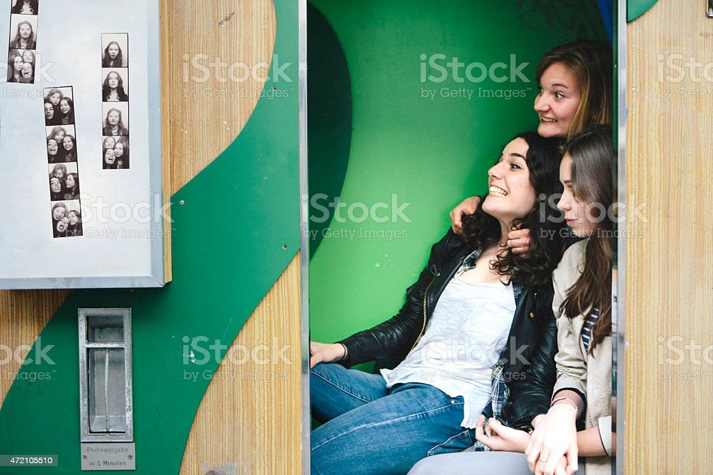 three teenager girls together in photo booth making faces stock photo