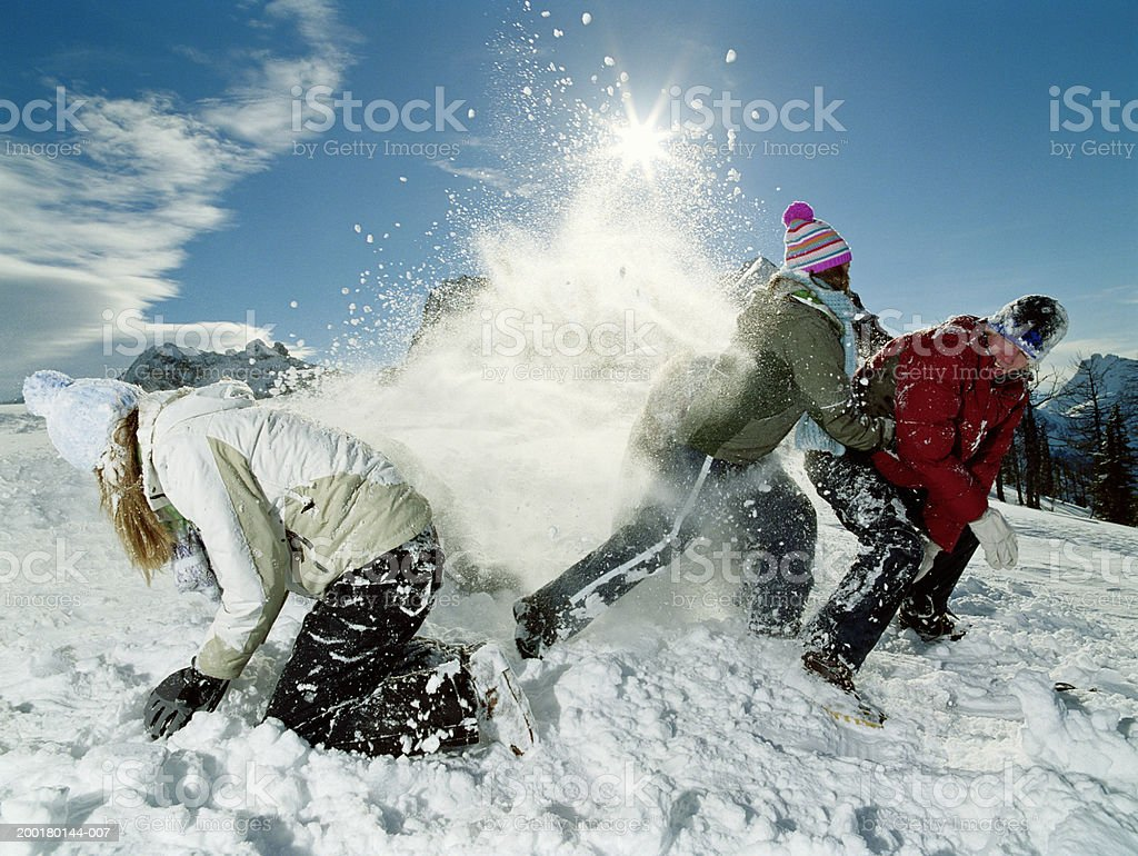 Three teenagers (15-17) roughhousing in snow, side view stock photo