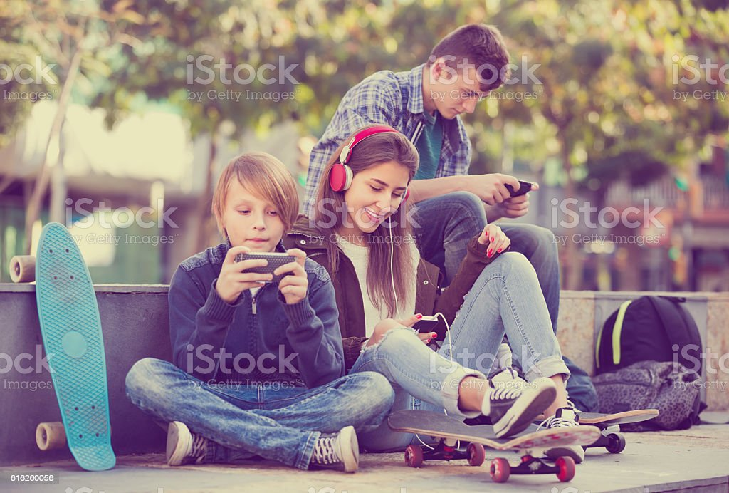 Three teenagers with phones outdoors stock photo