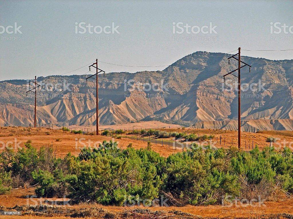 Three Telephone Poles Through Rugged Mountainous Terrain royalty-free stock photo