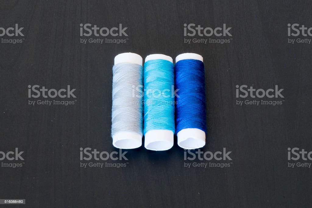 Three thread rolls in shades of blue stock photo
