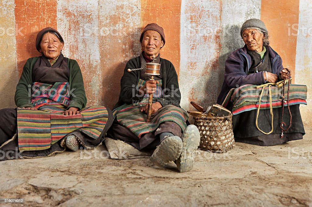 Three Tibetan women praying in Lo Manthang, Nepal stock photo