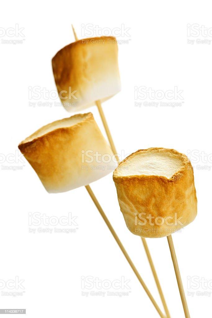 Three toasted marshmallows on sticks stock photo