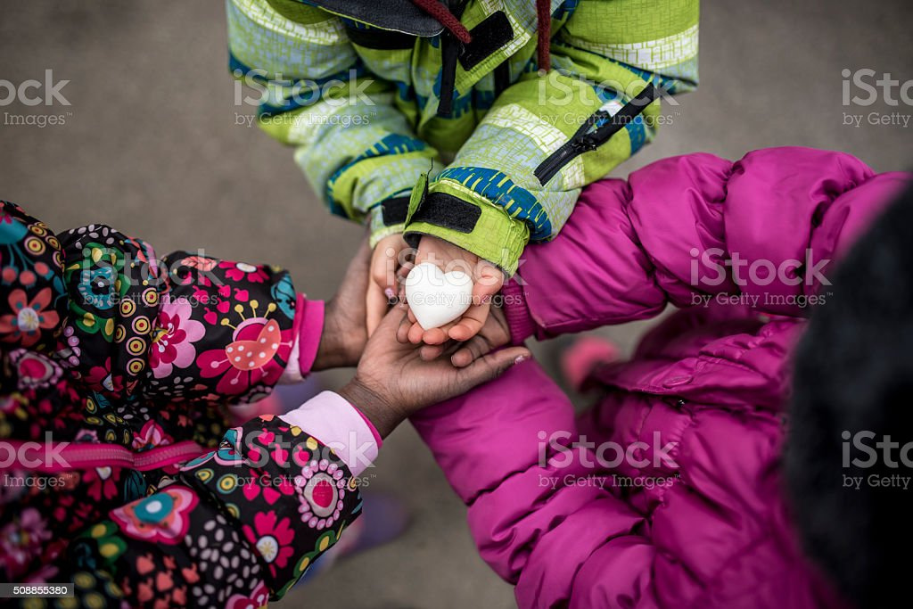 Three toddler girls holding their hands joined together with the stock photo