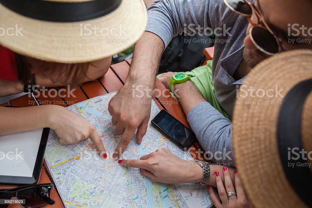 Three Tourists Pointing On Map stock photo
