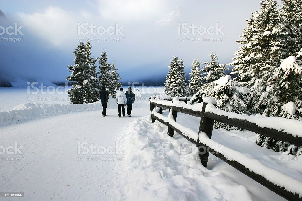Three tourists walk along snow covered path at Lake Louise royalty-free stock photo