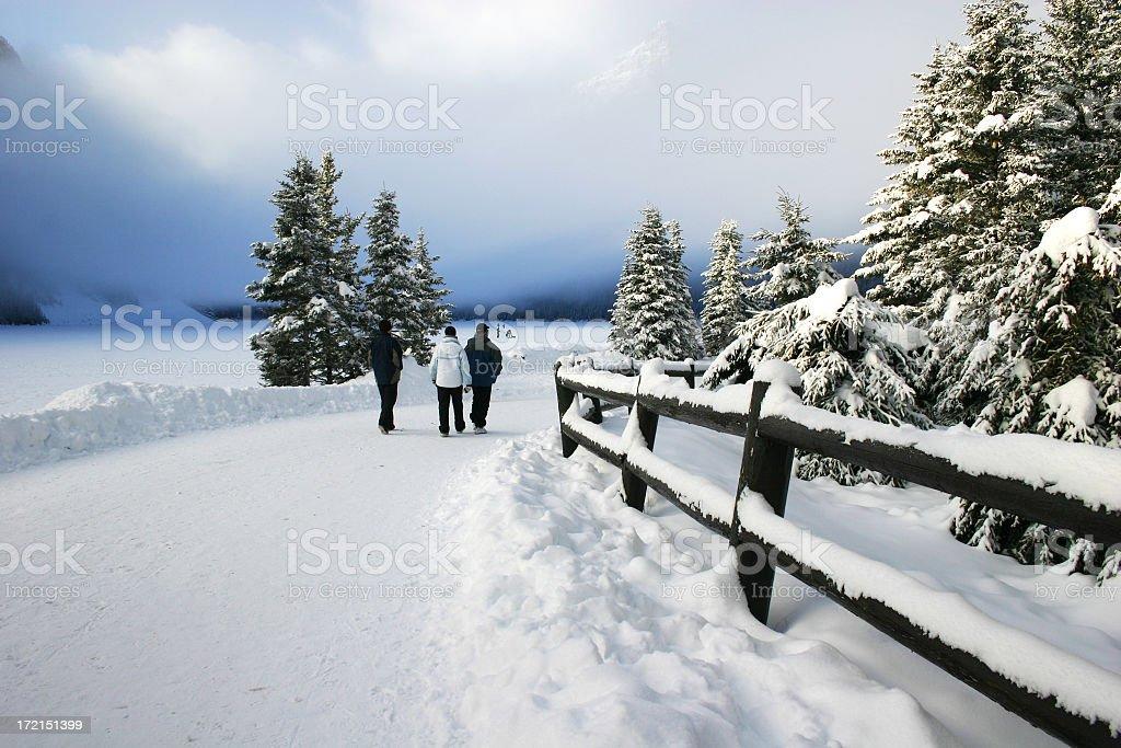 Three tourists walk along snow covered path at Lake Louise stock photo