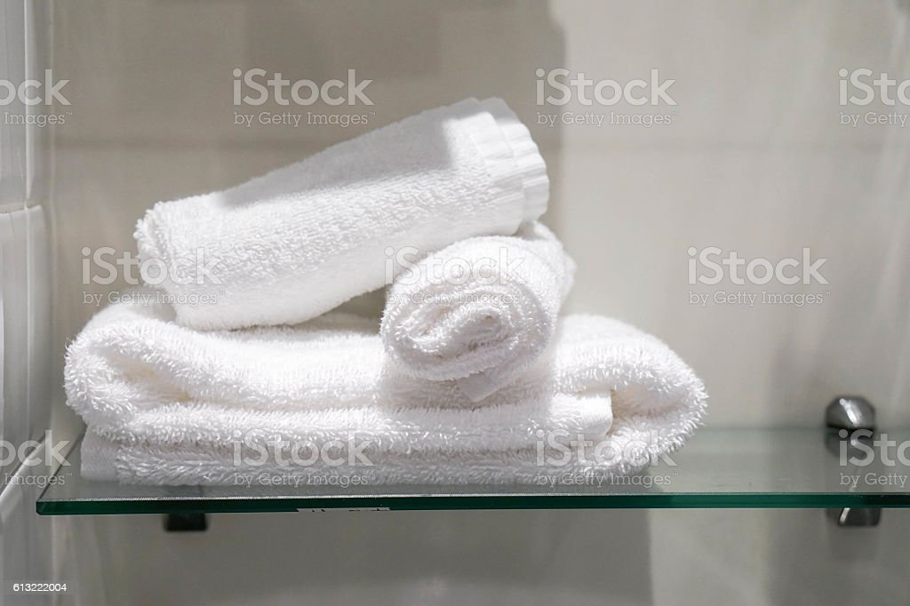 Three towels are placed on the shelf in the bathroom stock photo