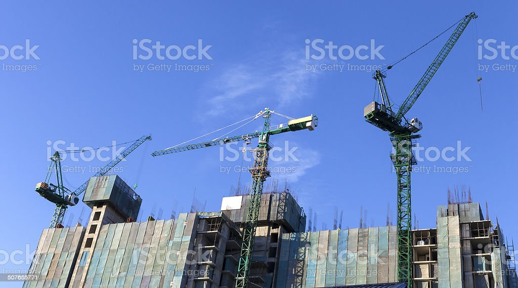 three tower cranes working on top of high-rise building construc stock photo