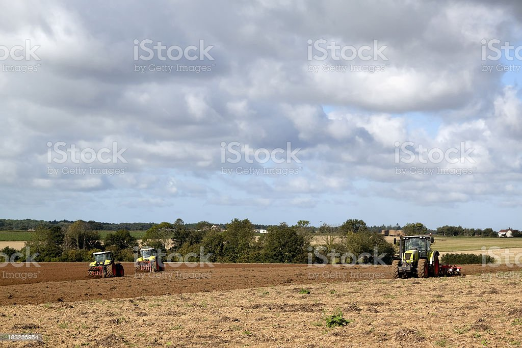 Three tractors ploughing a field in September royalty-free stock photo