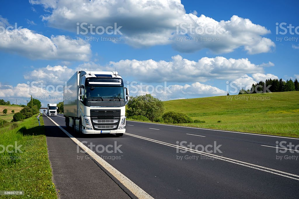 Three trucks driving on the road in a rural landscape. stock photo