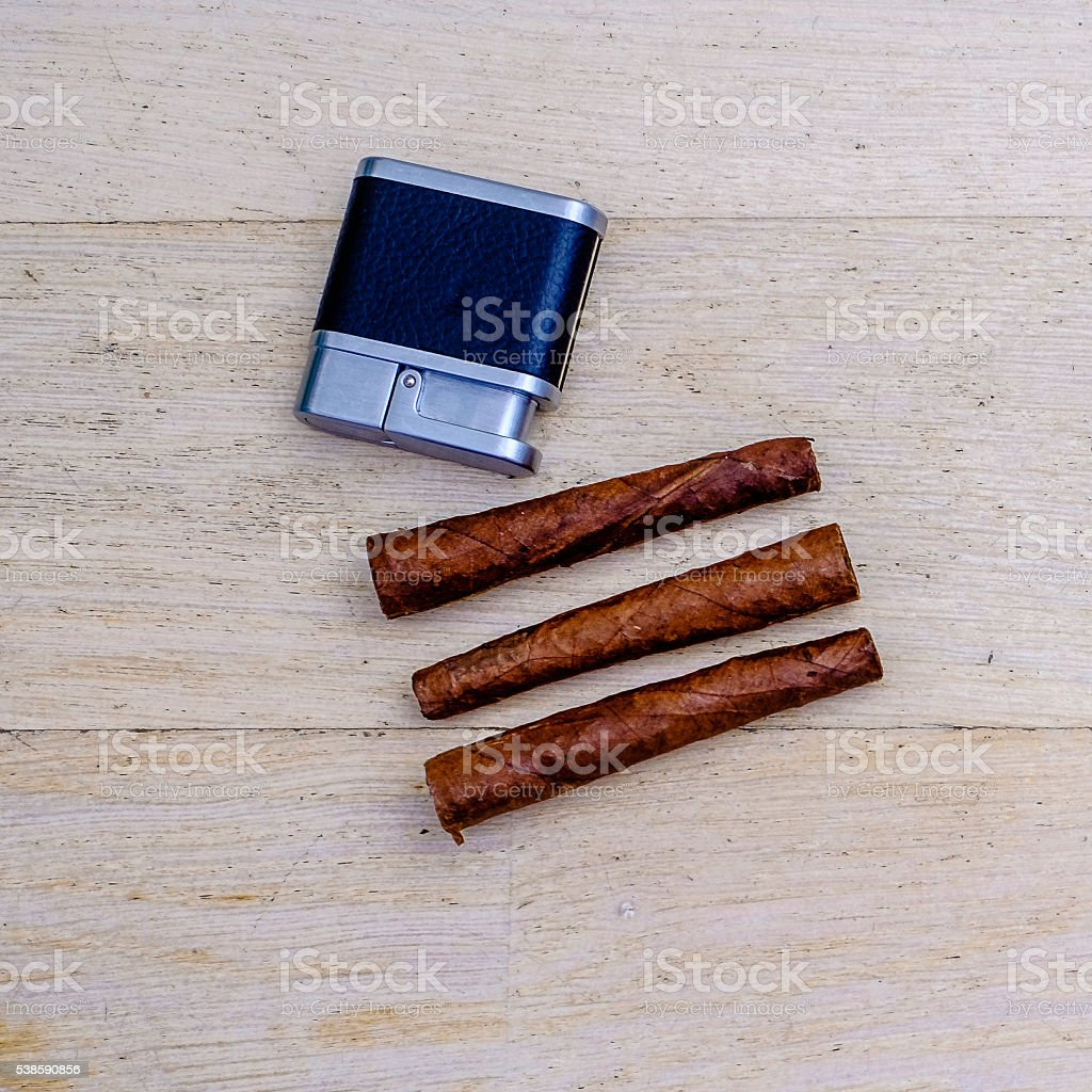 three Tuscan cigars and a lighter on a wooden floor stock photo