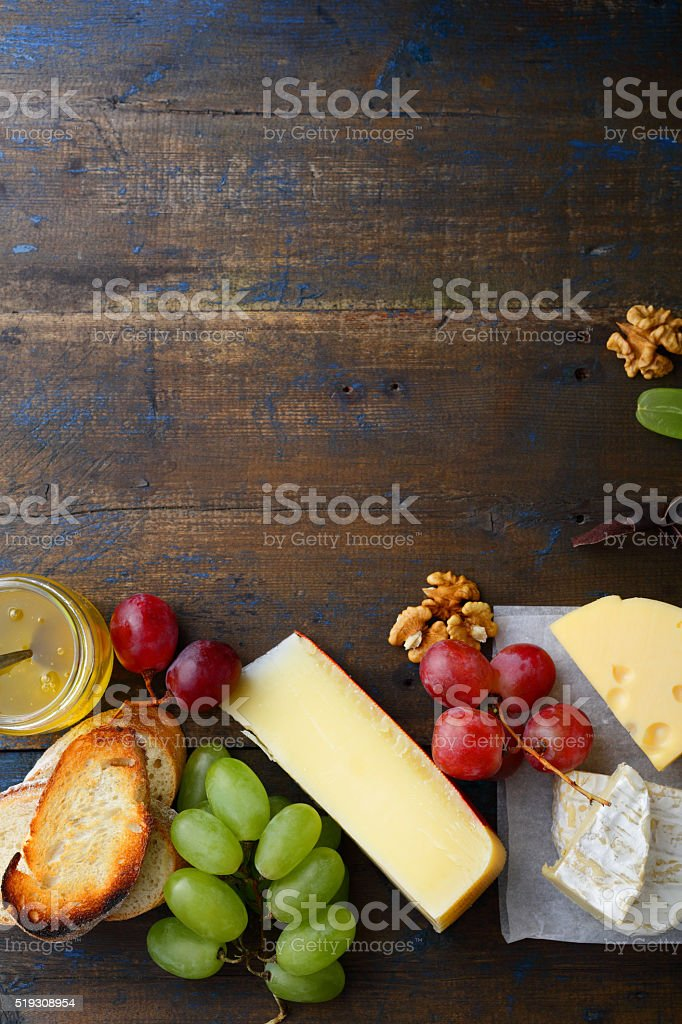Three types of cheese with grapes, honey, bread and walnuts stock photo