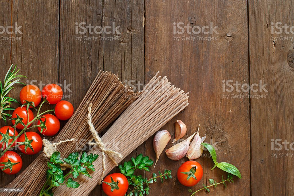 Three types of spaghetti, tomatoes and herbs stock photo