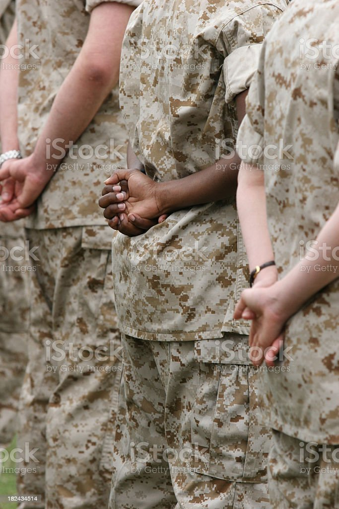 Three uniformed military members' backs are shown standing stock photo