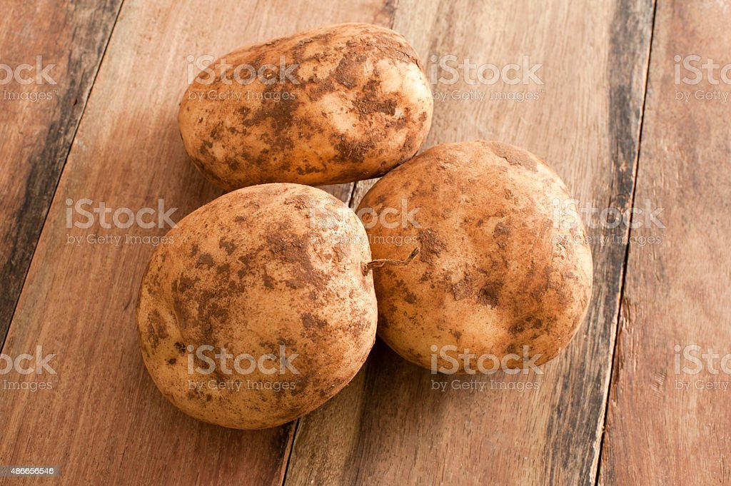 Three Unwashed Potatoes on a Wooden Table stock photo