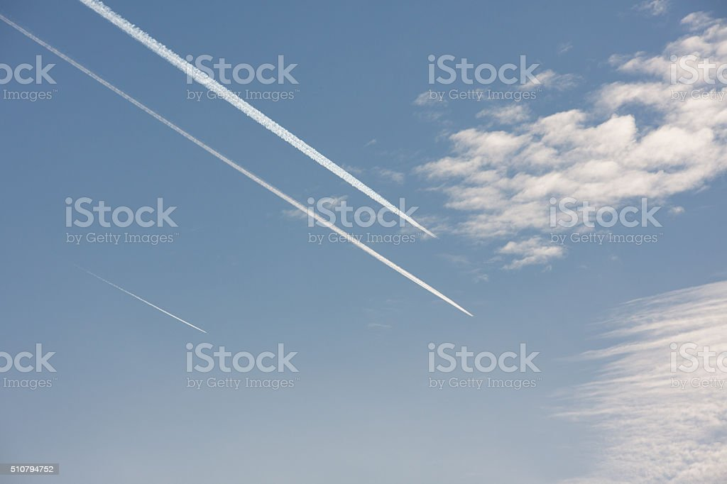 Three vapor trails in blue sky over Berlin, Germany stock photo