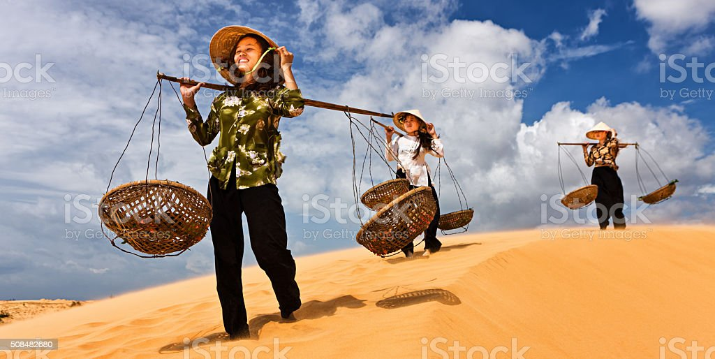 Three Vietnamese women crossing sand dunes stock photo