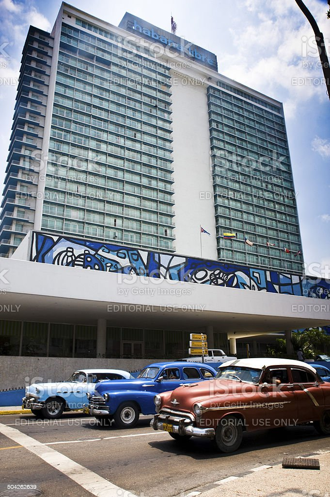 Three vintage cars at stoplight outside Havana Libre Hotel stock photo