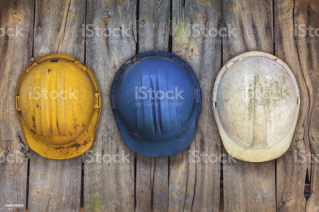Three vintage construction helmets on a wooden wall stock photo