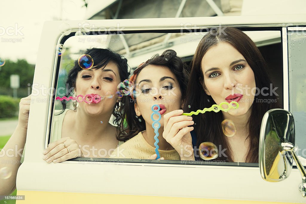 Three vintages girls blowing bubbles through open car door. royalty-free stock photo