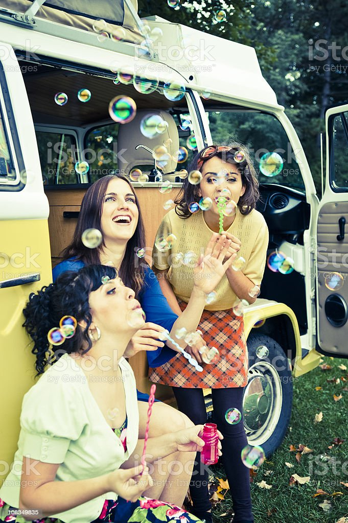 Three vintages girls making bubbles outdoors in summer, vertical. royalty-free stock photo