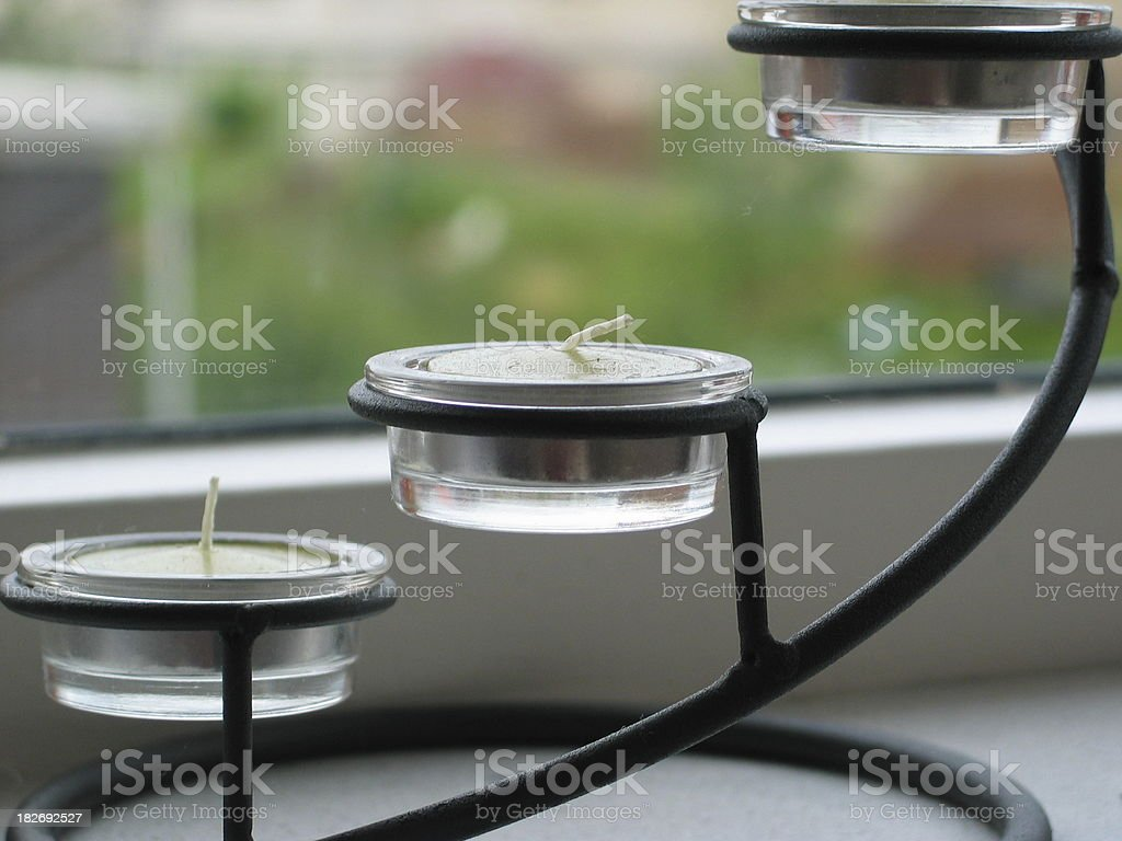 Three wax candles in a candleholder stock photo