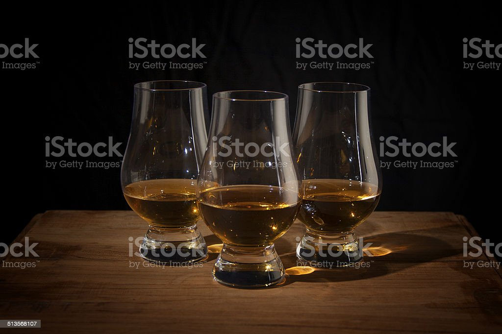 Three whisky glasses on a wooden table stock photo