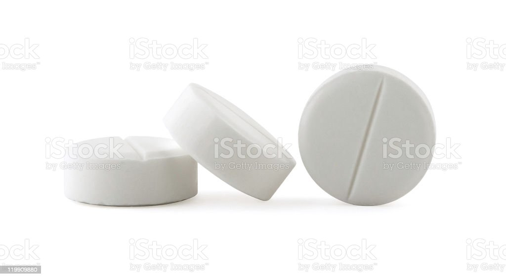 Three white aspirin one standing on side and others leaning stock photo