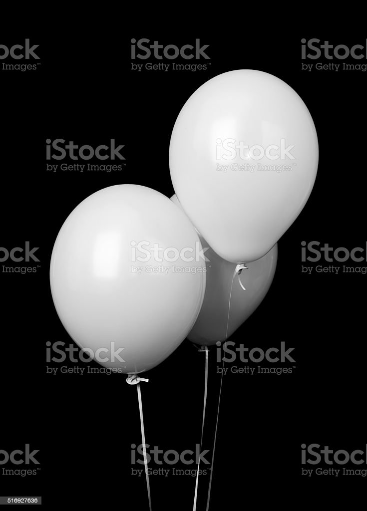 Three white balloons isolated on black stock photo