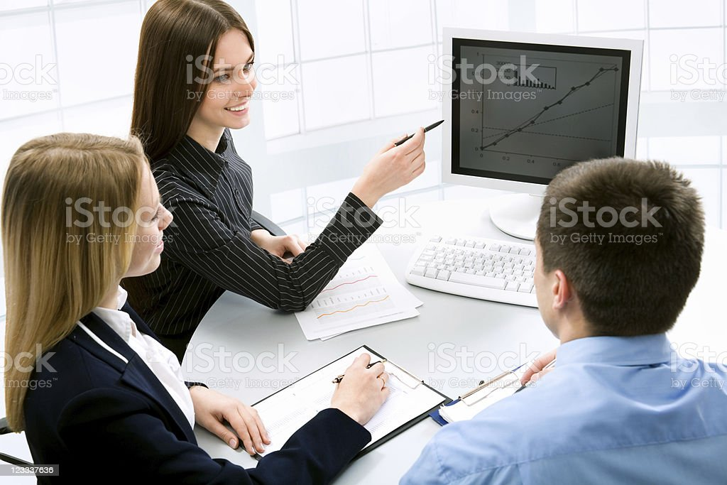 Three white collar workers conduct a business meeting  royalty-free stock photo