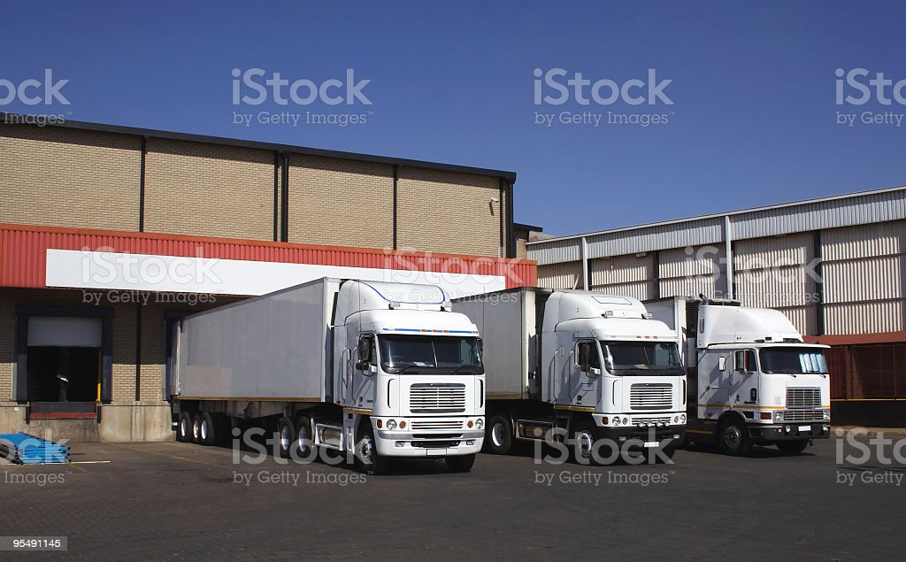 three white Freight trucks trailers at logistics warehouse loading docks royalty-free stock photo