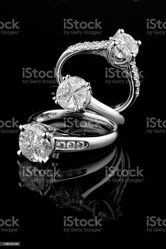 Three white gold diamond rings on black background royalty-free stock photo